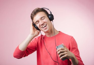 Portrait of a young handsome man with headphones smiling and listening a music with a smartphone.