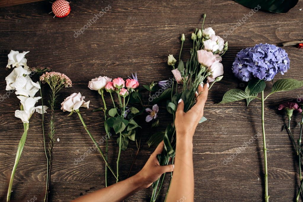 There are different flowers for collecting bouquet on the wooden table in flower shop