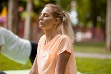 Young slender girl with closing eyes doing yoga exercises on the yoga mat on green grass in the park on a warm day. Yoga on the open air