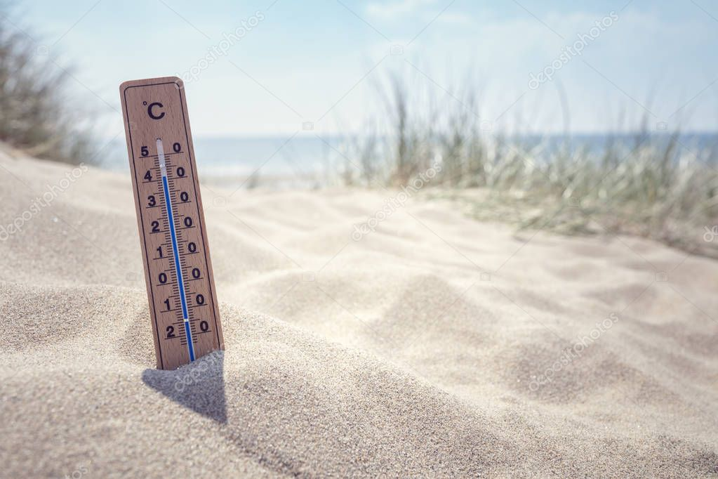 Thermometer on the beach showing high temperature  background
