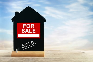 Real estate agent for sale sign with sold on house shape chalk blackboard
