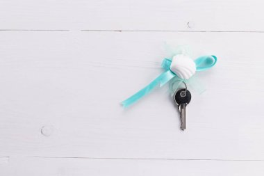 Silver keys on a wooden white backgound. Real estate concept