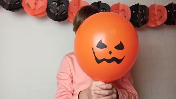 Chlapec v lékařské masce vykoukne zpoza baloonu, Helloween během pandemie koronaviru