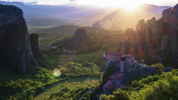 erstaunliche Aussicht auf das Meteora-Tal bei Sonnenuntergang, Strahlen, die über Felsen und über das Rousanou-Nonnenkloster und das St.-Nikolaus-Anapausas-Kloster laufen, Kastraki, Kalambaka, Thessalien, Griechenland - Zeitraffer