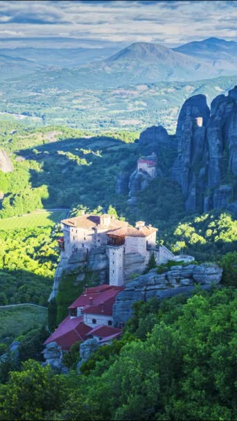 Vertical view of Meteora valley at sunrise, with shadows running over Rousanou nunnery and St Nicholas Anapausas monastery, Kastraki, Kalambaka, Thessaly, Greece - timelapse, vertical