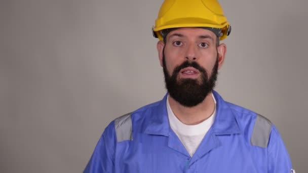 Porträt von jungen Arbeiter in gelben Helm erklären etwas und zeigen ok Geste auf grauem Hintergrund