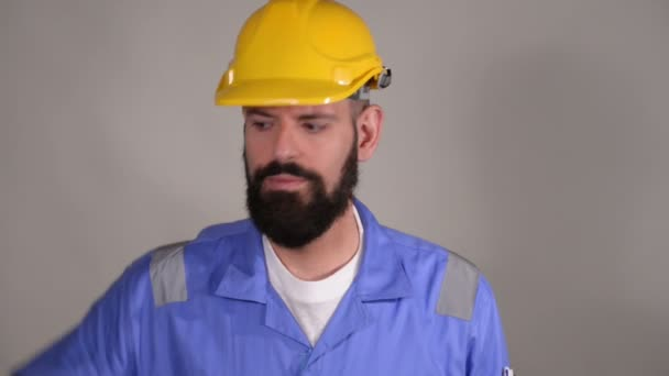Bearded worker in yellow helmet talking on the mobile phone with someone over grey background