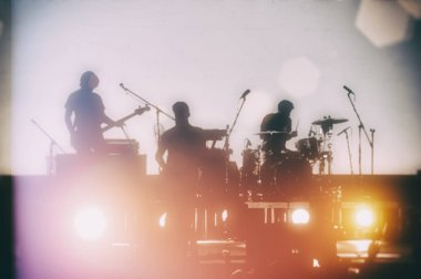 Silhouette of musical rock band on concert on blurred background