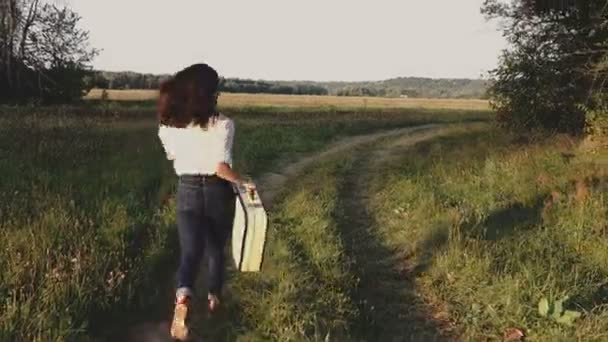 footage of beautiful young woman with vintage suitcase in field
