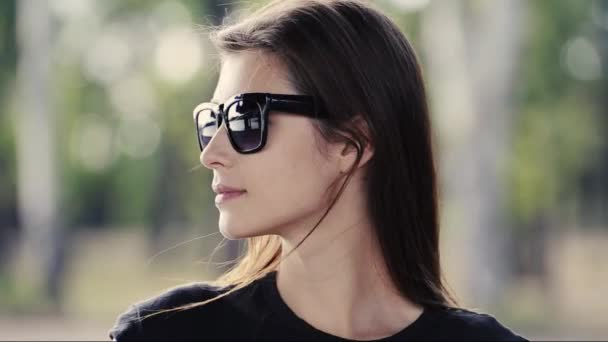footage of beautiful young woman in sunglasses in nature