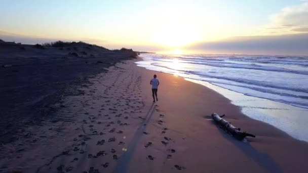 Aerial panning with drone on young attractive man jogging on the beach at sunrise. Running workout practice in fitness and healthy lifestyle concept.