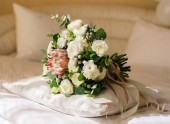 Classic white and green bridal bouquet with rosy protea and ranunculus flowers lays on the bed. Classic wedding concept.