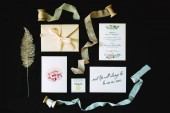 Set of wedding decorations: calligraphy, invitation cards, envelope, lace and ribbons on black background. Flat lay, close up. Rustic wedding concept.