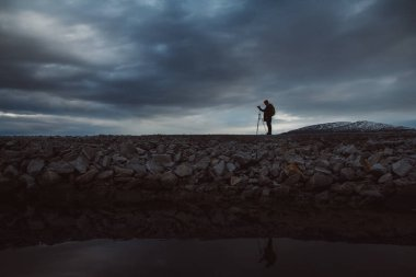 Silhouette of a photographer or traveler with tripod standing on stone. Background of a dramatic sky. Hazardous working conditions and human silhouette