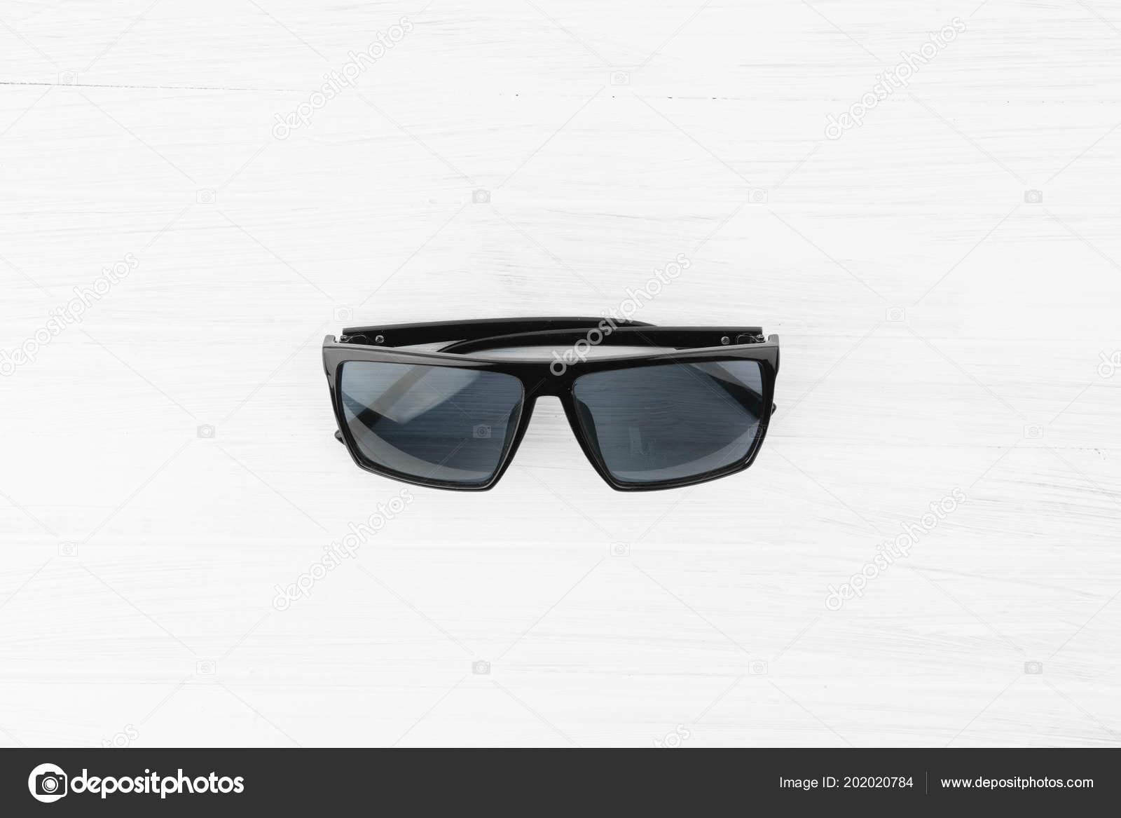 5bae7907e8 Gafas de sol elegantes negro con tinte azul sobre fondo blanco de madera  superior ángulo visión — Foto de ...