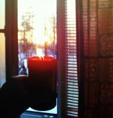 Piros égő gyertya a kezében a téli napfelkelte háttér