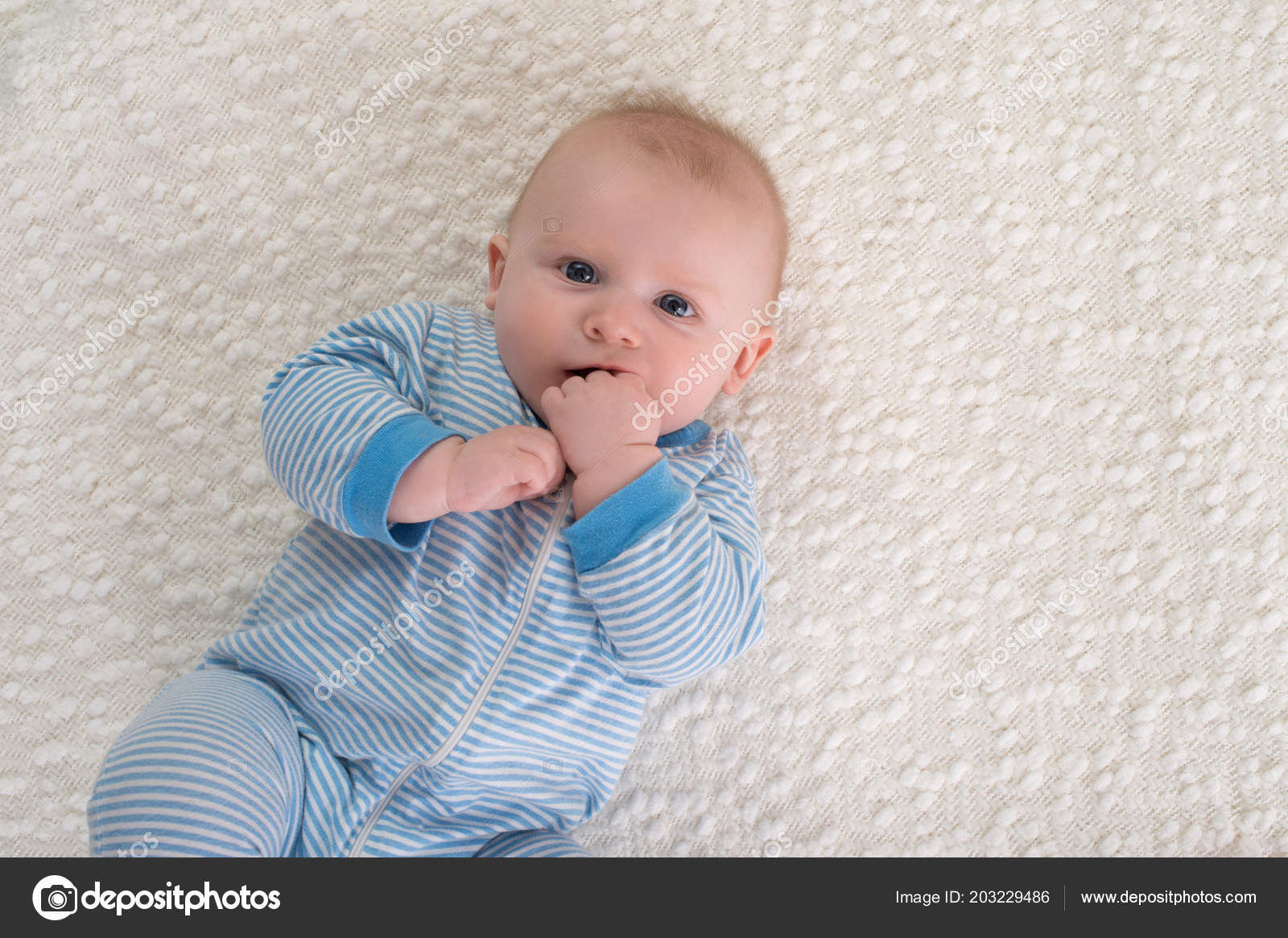 58389889251 A 2 month old baby boy lying on his back on a white blanket. He is wearing  blue and white striped pajamas and has his hand in his mouth and is looking  ...