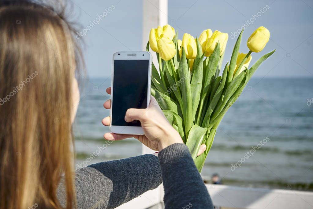 woman photographing yellow tulips against the sea