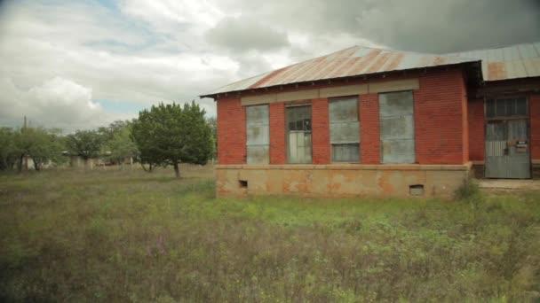 široký záběr na opuštěné cihlové budovy v zarostlé lot