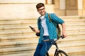 fiatal diák a szemüveg és a kerékpár, a kerékpár, az utcán Egyetem előtt állt, és látszó-on mozgatható telefon, mosolyogva, szociális média ellenőrzése