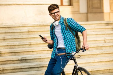 Young student with glasses and bike standing on his bike on the street in front of university and looking at mobile phone, smiling, checking social media stock vector