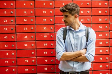 Waiting for delivery. Young man, smart casual, at the mailboxes post, waiting for his order to arrive