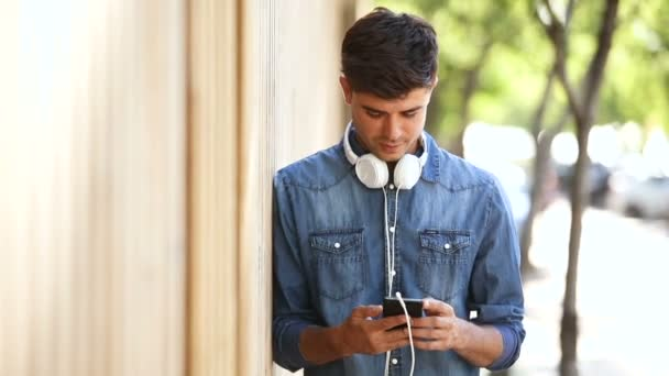 handsome young man listening music through headphones and using mobile phone