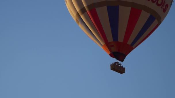 Közeli kép: egy piros-fehér-kék léggömb a kék égen. Az emberek repülni a léggömb a kosárban. Lassan emelkedik a léggömb.