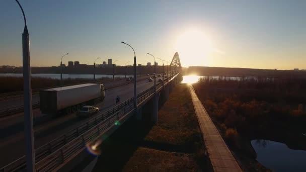 Novosibirsk, Rusko - 2 říjen 2018: cesta přes most při západu slunce, kdy automobily a motocyklista se pohybují. Slunce se odráží ve vodě a vyvolá zvýraznění na fotoaparátu.