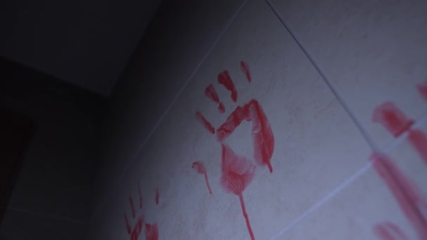 Bílá stěna s tištěnou palmou a barevným nátěrem. Hodně otisků prstů. V temné místnosti se ztlumí světlo. Koncept hrůzy. Close-up.