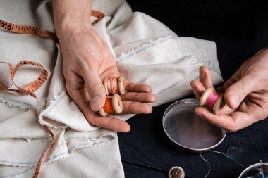 Tailor holding spool of thread, craftsman.