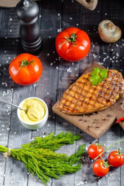 grilled kebab grilled meat steak lies on a wooden vintage old board rustic, chili, with tomatoes, sauce, dill onions, on the table on top, side, bottom shot angle, fork and knife mushrooms