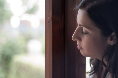 Sad and anxious beautiful woman is worried and looking through the window