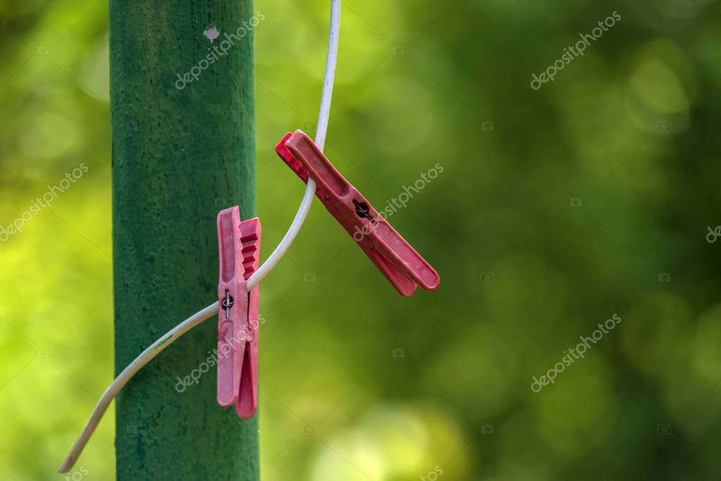 Red plastic clothespins on a rope hanging outside house