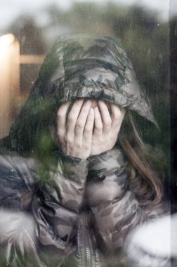 Beautiful woman with hooded jacket is worried and looking through the window and holding her head