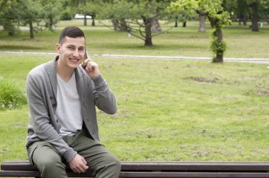 Portrait of young guy in the public park sitting on wooden bench and using his smart phone