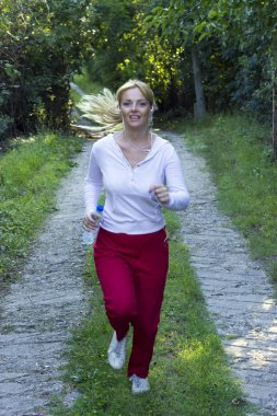 Attractive blonde woman with earphones running through the park and feeling relaxed listening to music