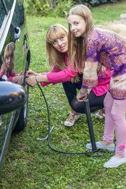 Woman with her daughter pumping tire