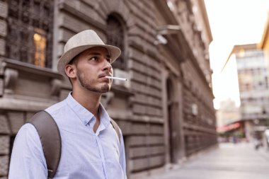 Handsome Well Dressed Young Man with Hat, Sunglasses and Backpack Standing in the City Center and Smoking a Cigarette