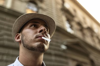 Handsome Well Dressed Young Man with Hat Standing in the City Center and Smoking a Cigarette