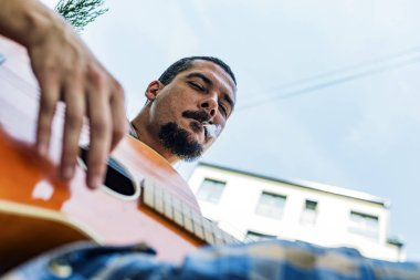 Man with Moustache and Beard, Playing a Guitar and Enjoying Marijuana Cigarette