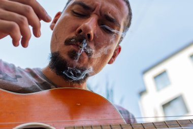 Man with Moustache and Beard, Playing a Guitar and Enjoying Marijuana Cigarette