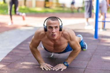 Handsome Man With Headphones in Perfect Body Shape Doing Push ups Outside in the Park