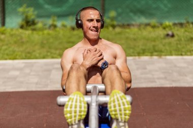 Young Muscular Man With Headphones in Perfect Body Shape Doing Sit Ups in Public Park
