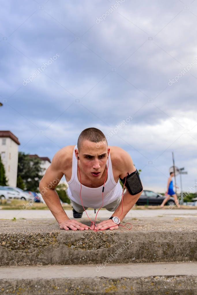 Young male runner doing push ups in City
