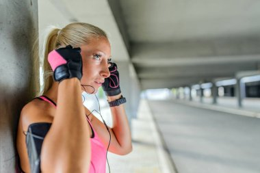 Portrait of young woman look side, standing outdoors with earphones. Female runner relaxing after workout.