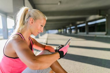 Young sporty woman with headphones taking a break after hard training and using mobile phone.
