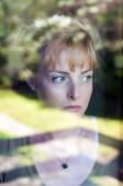 Portré szomorú nőt keres az ablakon