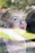 Portré vonzó nőt keres az ablakon, és mosolyogva