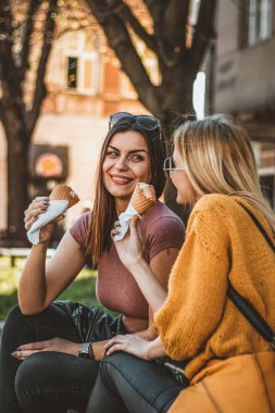 Attractive Brunete and his Beautiful Blond Girlfriend are Sitting in the Public Park and Enjoying in Cold Ice Cream.